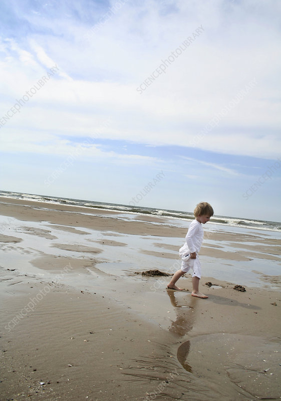 Boy walking on a sandy beach