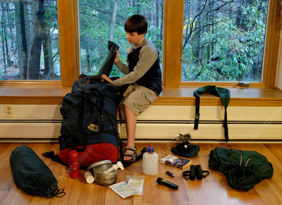 Boy packing camping gear for a trip