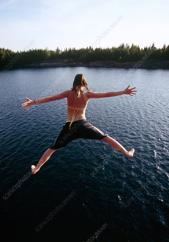 Girl jumping into a lake