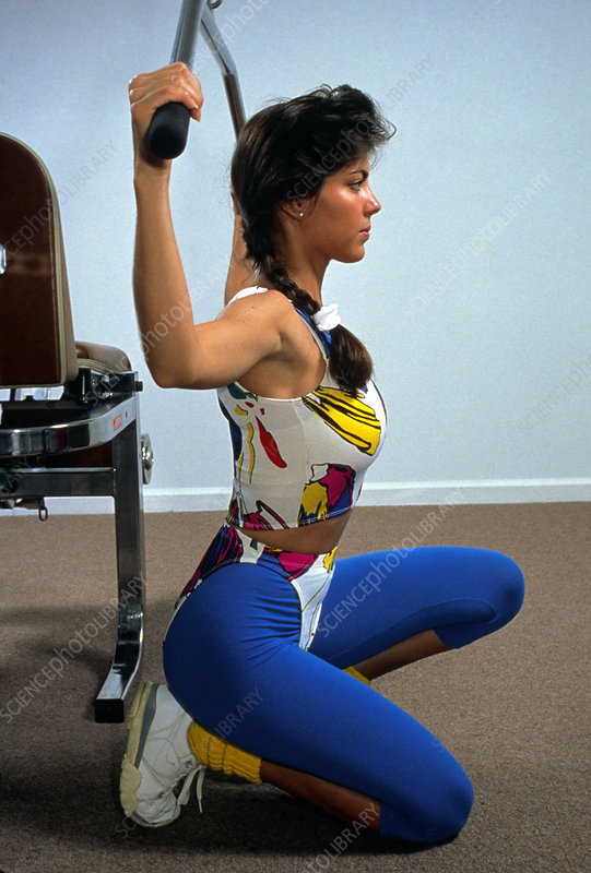 Young woman exercising on weight-training machine