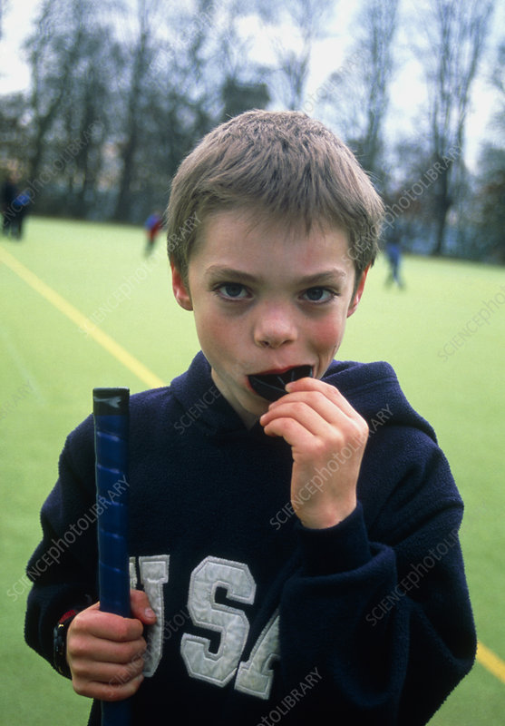 Boy putting gumshield in mouth for hockey game