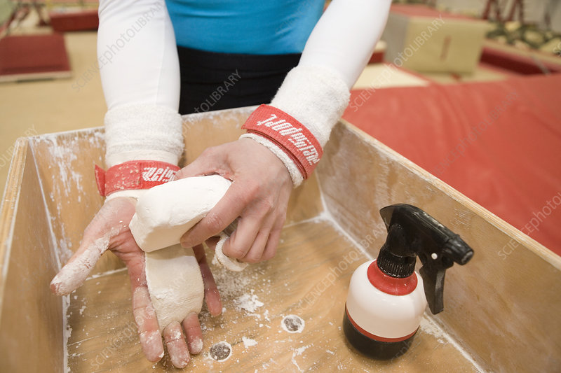 Gymnast rubbing hands with chalk