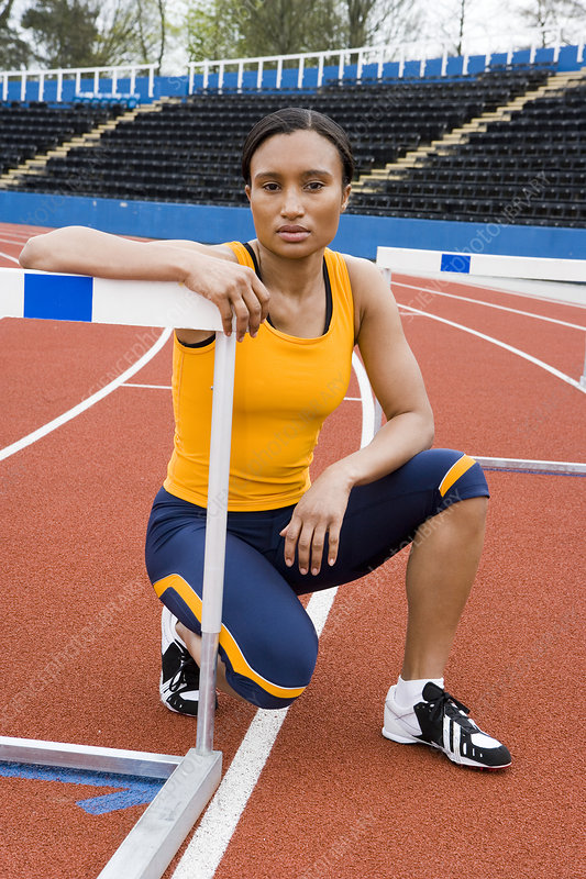 Athlete crouching next to a hurdle