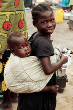 Ugandan girl carrying a baby