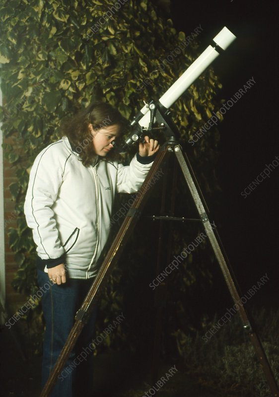 Astronomer using a refractor telescope