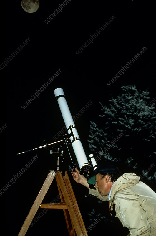 Amateur astronomer observing moon with telescope