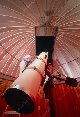 Amateur astronomer uses a reflector telescope