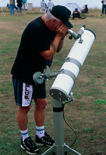 Amateur astronomer using telescope during eclipse