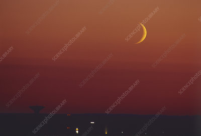 Crescent moon over a satellite dish