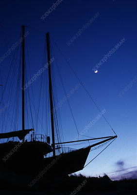 Moon above sailboat