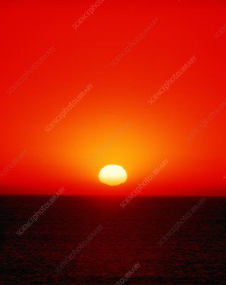 Sun (with distorted disc) setting over the ocean