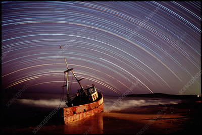 Star trails over rusted boat wreck