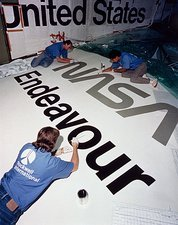 Painting insignia on wing of Shuttle Endeavour