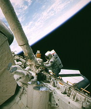 Astronaut using snag-type device during EVA.