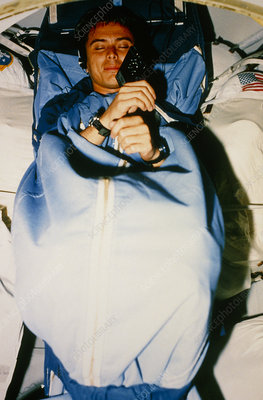 Astronaut in sleep restraint