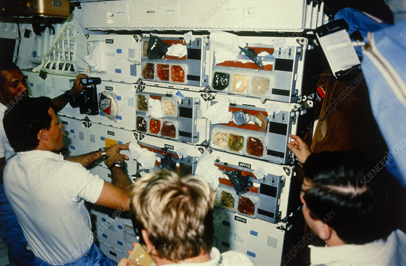 Astronauts select food from space shuttle galley