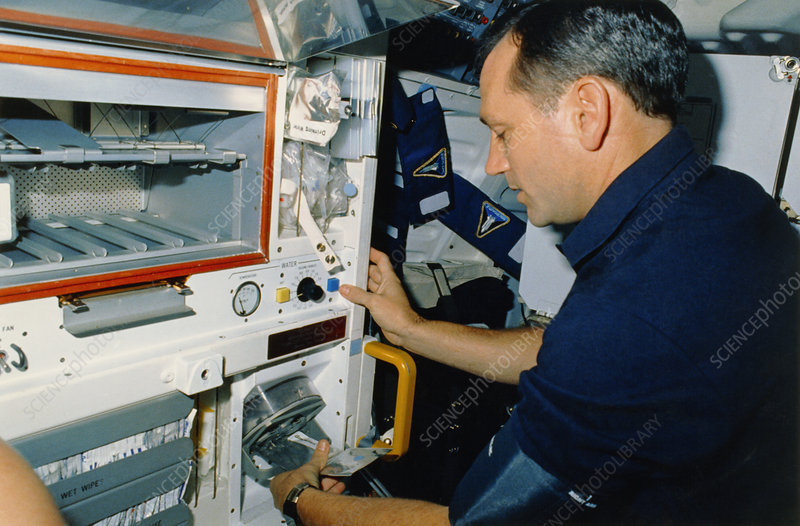 Astronaut Akers rehydrating food package