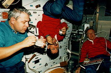 Shuttle astronauts taking a meal