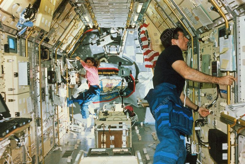 Astronauts working in a laboratory on the shuttle