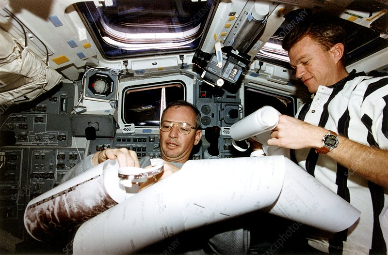 Astronauts reading a computer print-out.