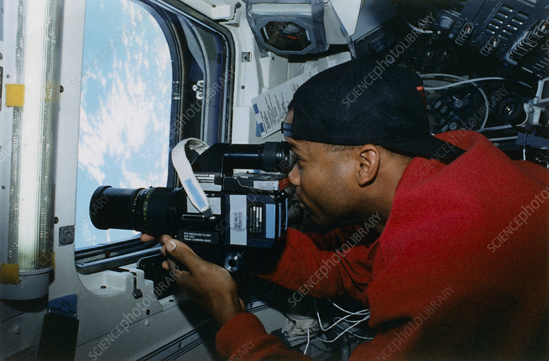 Astronaut uses a video camera on the space shuttle