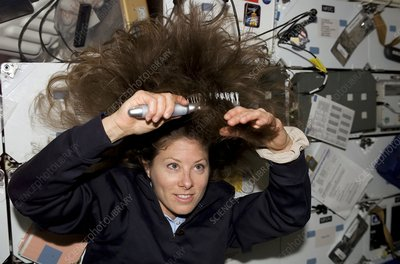 Shuttle astronaut combing her hair, STS-118