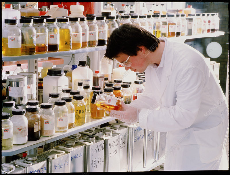 Technician with shelves of oil samples.