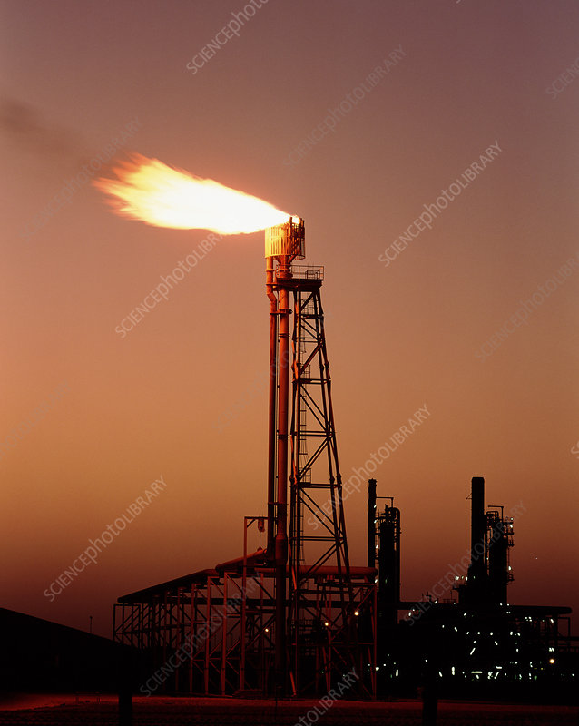 Gas flare in front of an oil refinery