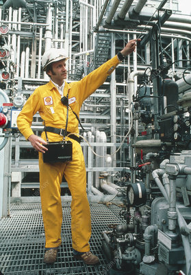 Technician tests gas piping at an oil refinery