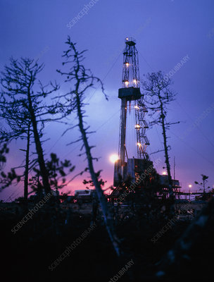 Derrick at an oil well in the evening