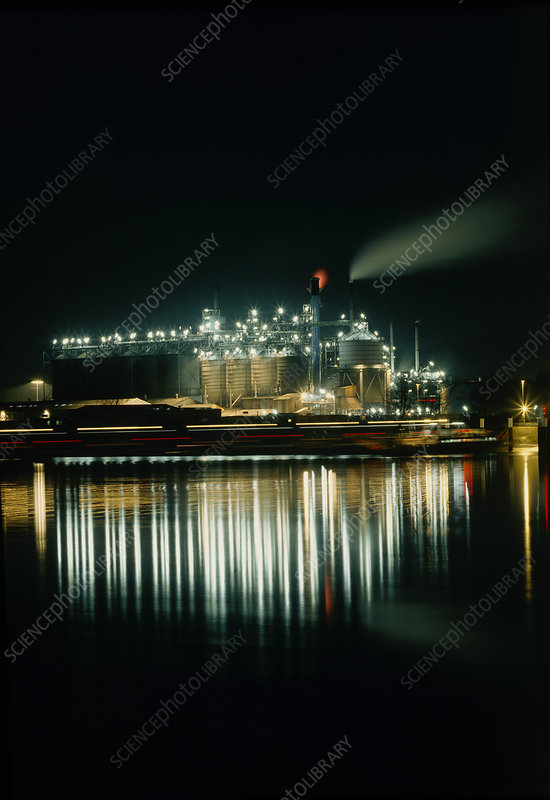 Oil refinery at night with reflections from water