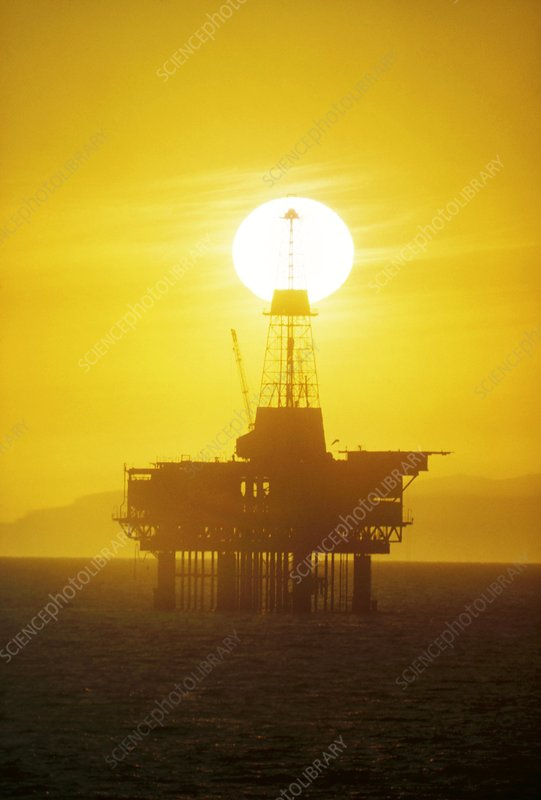 Sunset behind offshore oil rig - CA