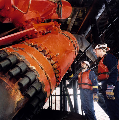 Technicians inspect a pipe on an oil rig