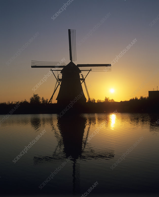 Sun rising behind a windmill