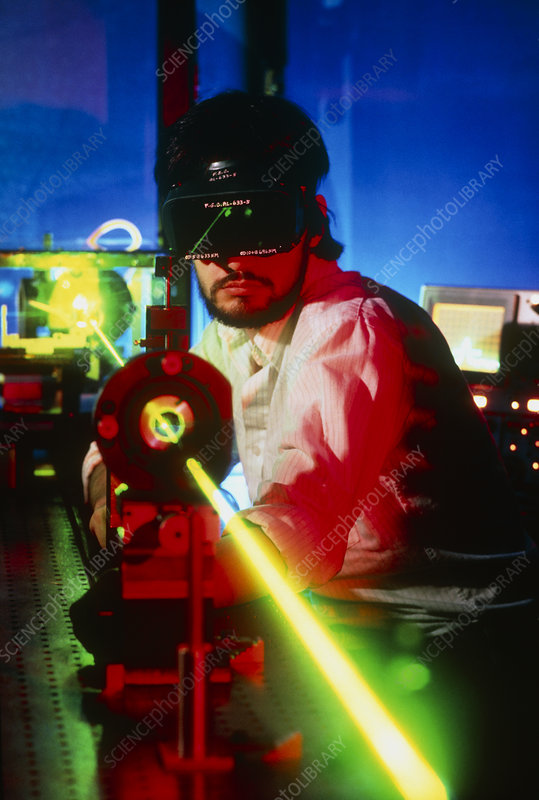 Researcher at optical bench working with a laser