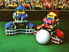 Two Lego footballers with a ball at RoboCup-98