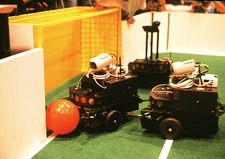 Robots trying to score a goal at RoboCup-98, Paris