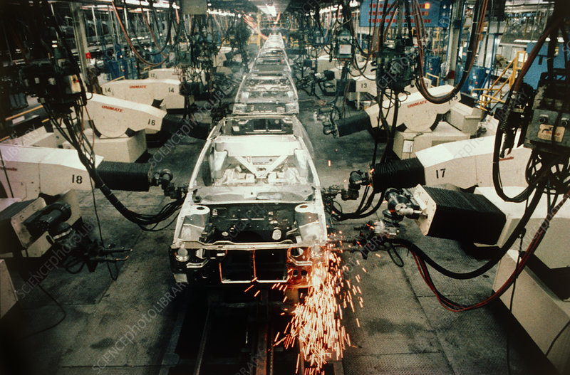 Robots welding on car assembly line