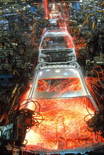 Robot arms welding cars on a production line