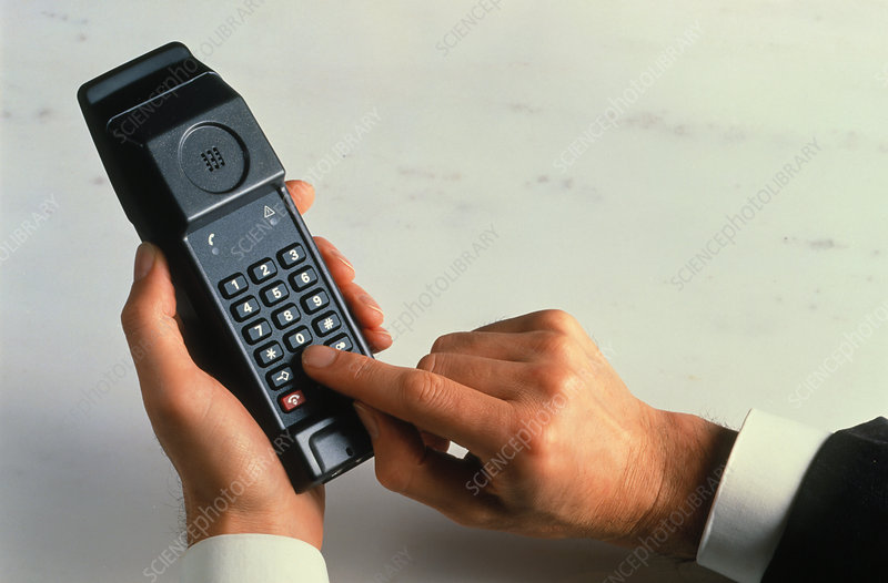 Man dialling a number into a cellular phone