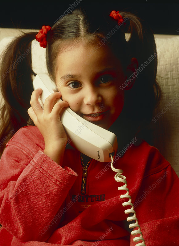Young girl talks on a telephone