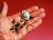 Hand holds transistors from the 1960s to 1990s