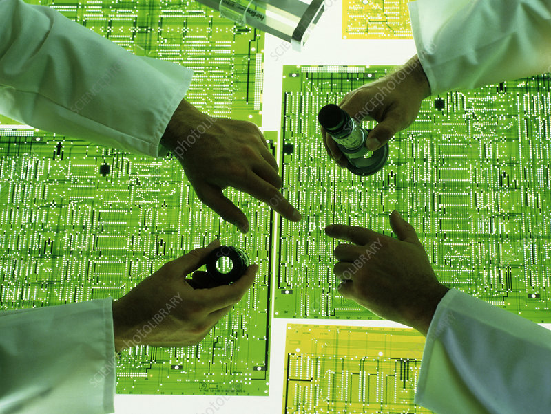 Technicians examine a circuit board design