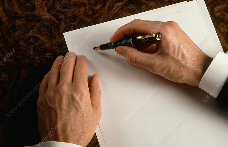 Businessman begins writing on a sheet of paper