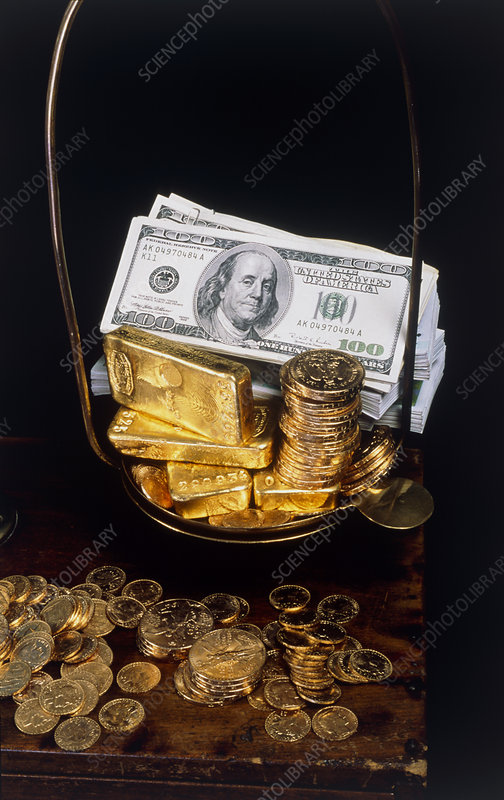 Banknotes, coins and gold bars on weighing scales