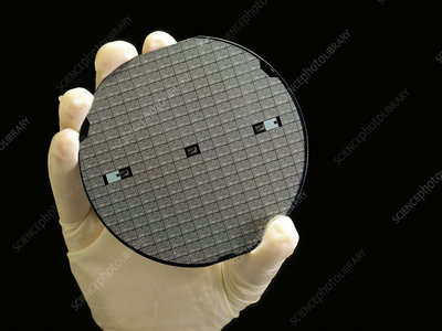 Gloved hand holding processed silicon wafer