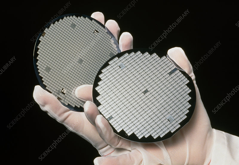 Gloved hands holding processed silicon wafers
