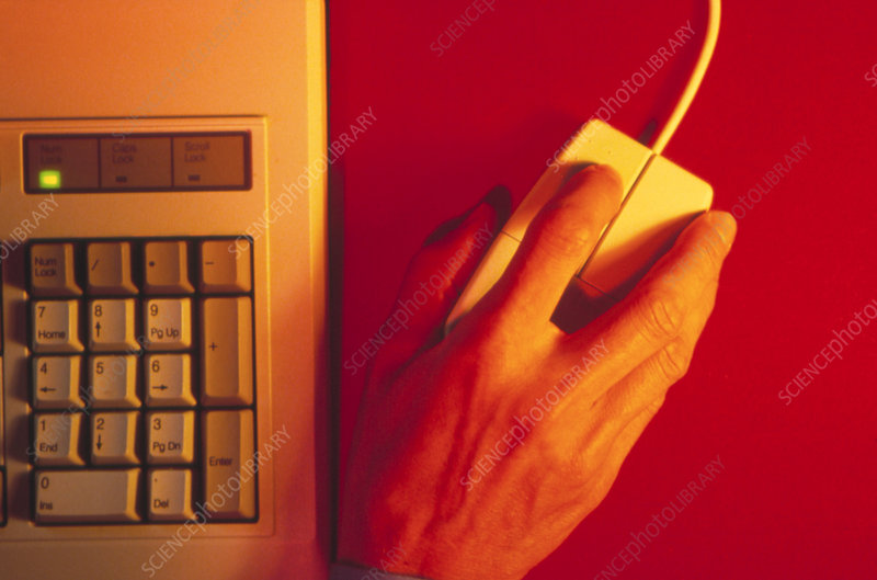 Hand operates a computer mouse beside a keyboard