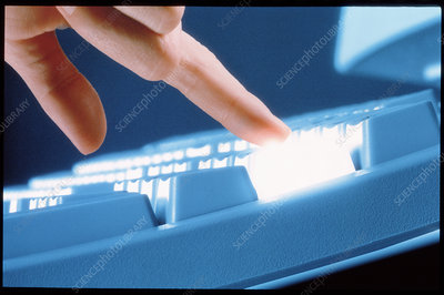 Computer keyboard key lit up as it is touched