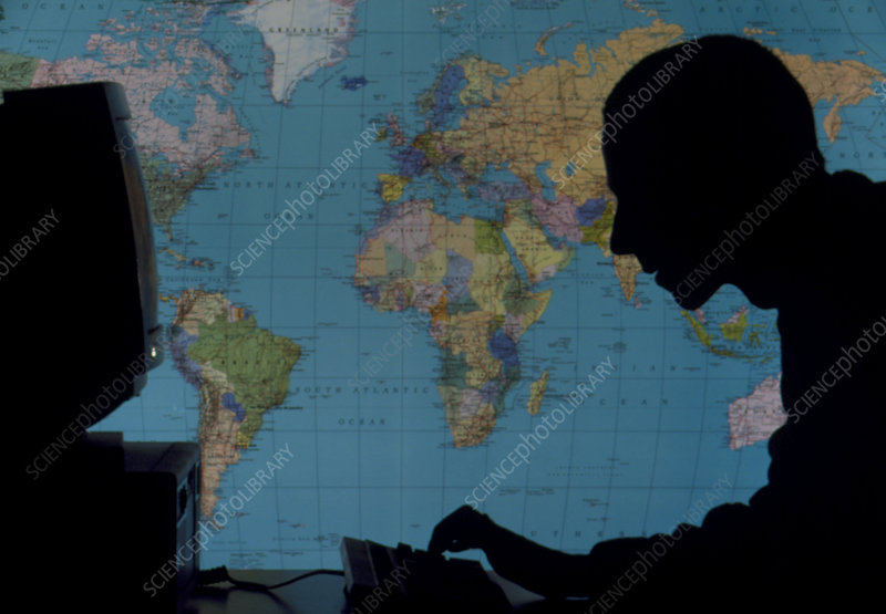 Man using computer against world map
